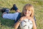 Garçon souriant et couché sur l'herbe avec le ballon de soccer