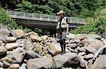 Homme avec chapeau de paille debout et tenant la canne à pêche