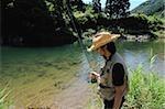 Homme avec chapeau de paille et de tenir la canne à pêche