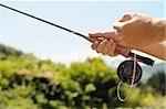 Mains tenant la canne à pêche et un moulinet