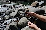 Mains tenant la canne à pêche