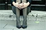 jambes d'une femme assise sur un escalier, gros plan