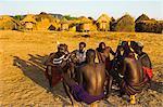 Karo elders sitting with guns on wooden head-rests with kalashnikov, Kolcho village, Lower Omo valley, Ethiopia, africa