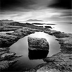 Erratic in tidal pool on isle of Taransay, looking towards Toe Head on South Harris, Outer Hebrides, Scotland, United Kingdom, Europe