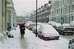 Frau mit Sonnenschirm und Autos fallen im Winter im Schnee in West Kensington, London, England, Großbritannien, Europa
