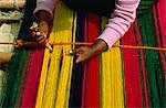 Une femme indienne de tissage de tapis dans le petit village de lac Titicaca, en Bolivie, en Amérique du Sud