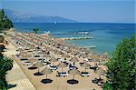 Beach umbrellas on coast near Dassia, on the island of Corfu, Ionian Islands, Greek Islands, Greece, Europe