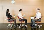 Employés de bureau assis dans des chaises avec des documents
