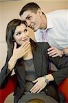 Office worker whispering in co-worker's ear