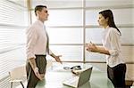 Businessman in office talking to businesswoman