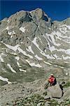 Trekker reposant sur un rocher dans les hautes montagnes du massif central des Picos de Europa en Cantabrie, Espagne, Europe