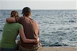 Rear view of a couple sitting at the seaside, Italian Riviera, Mar Ligure, Genoa, Liguria, Italy