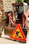 Road construction sign near an earth mover, Vernazza, La Spezia, Liguria, Italy