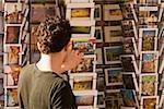 Rear view of a man choosing postcards, Piazza Della Cisterna, San Gimignano, Siena Province, Tuscany, Italy