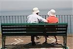 Rear view of a couple sitting on a bench at seaside, Via Aniello Califano, Bay of Naples, Sorrento, Sorrentine Peninsula, Naples Province, Campania, Italy