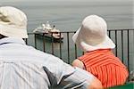 Rear view of a couple looking at a cruise ship, Via Aniello Califano, Bay of Naples, Sorrento, Sorrentine Peninsula, Naples Province, Campania, Italy