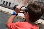 Vue arrière d'un garçon regardant à travers une paire de jumelles, la baie de Naples, Naples, Province de Naples, Campanie, Italie