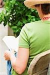 Rear view of a woman sitting on a bench and reading a book, Cinque Terre, Manarola, La Spezia, Liguria, Italy