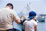 Vue arrière d'un homme avec un garçon assis au bord de la mer, Riviera italienne, Santa Margherita Ligure, Gênes, Ligurie, Italie
