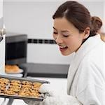 Gros plan d'une jeune femme tenant un plateau de biscuits et souriant
