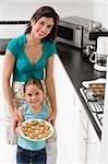 Jeune femme avec sa fille tenant une assiette de biscuits dans la cuisine