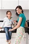 Portrait d'une jeune femme souriante avec sa fille dans une cuisine