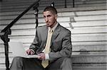 Portrait d'un homme assis sur un escalier et à l'aide d'un ordinateur portable