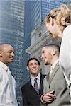 Profil de côté d'une femme d'affaires permanent avec trois hommes d'affaires