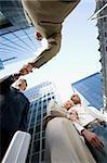 Vue d'angle faible d'une femme d'affaires avec sa tête sur l'épaule un homme d'affaires et de deux hommes d'affaires, serrant la main