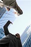 Vue d'angle faible de deux hommes d'affaires donnant High-Five et souriant