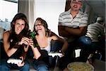 Deux jeunes femmes griller avec des bouteilles de bière et un jeune homme debout à côté d'eux