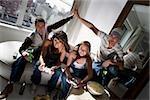 Deux jeunes femmes jouant des jeux vidéo et les deux jeunes hommes faisant cinq à côté d'eux