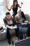 Deux jeunes hommes et une jeune femme jouant le jeu vidéo