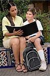 Female teacher checking a file of a schoolgirl
