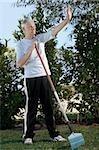 Senior homme tenant un râteau et montrant un panneau d'arrêt dans un jardin