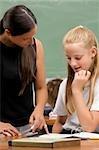 Female teacher teaching a schoolgirl in a classroom