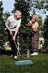 Homme Senior engrangent un jardin avec une femme senior debout derrière lui
