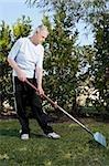 Homme Senior ratissage dans un jardin
