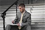 Homme d'affaires à l'aide d'un ordinateur portable sur l'escalier