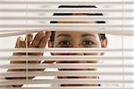 Businesswoman behind blinds