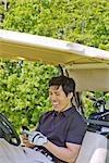 Homme au Golf Cart lecture Message texte