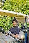 Homme en tenant le téléphone cellulaire de voiturette de Golf