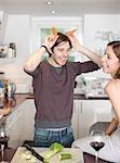 Homme des cornes avec carottes dans cuisine