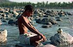 Pilgrim meditating by River Ganges, Rishikesh, India, Asia