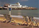 Chaises longues sur la Promenade donnant sur la plage déserte et Pier Theatre au début de la saison estivale, West Cliff, Bournemouth, Dorset, Angleterre, Royaume-Uni, Europe