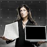femme tenant un ordinateur portable et un journal