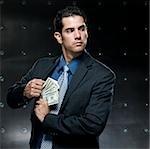 businessman putting cash into his coat