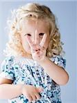 kleines Mädchen hält drei Finger