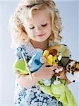 kleines Mädchen mit einem Arm voller ihre Spielsachen