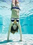teenage girl doing a handstand under water